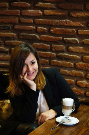 Beautiful woman drinking latte at a cafe table photo