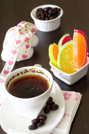 Cup of coffee and jujube sweets on the table photo
