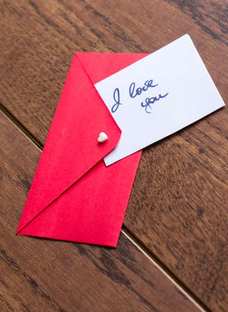 Red envelope with note, hearts and rose petals photo