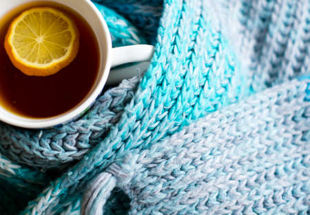 convalesce: Winter time: cup of hot tea with lemon and scarf