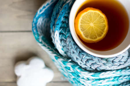 Winter time: cup of hot tea with lemon and scarf