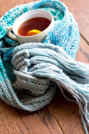 Cup of Hot tea in scarf with cinnamon sticks and lemon photo