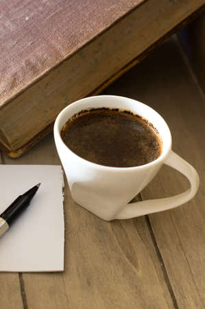 Cup of black coffee and old books photo