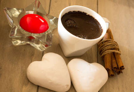 Cup of black coffee, beans, candle and cookies photo