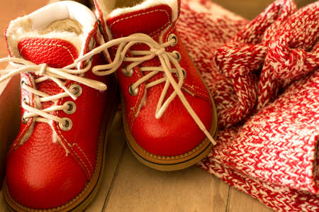 Red children winter shoes on the wooden photo