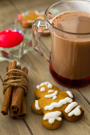 Glass of cacao, cookies and cinnamon on the wooden table photo