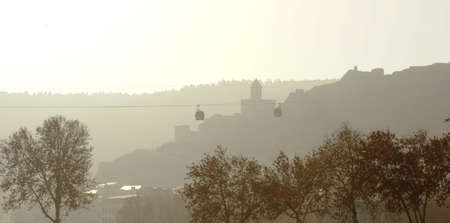 Misty morning in Old Tbilisi with view of Narikala castle and domes of ancient churches
