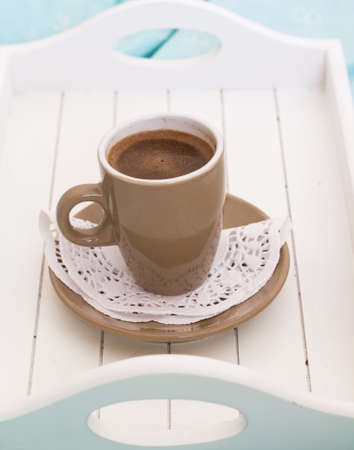 Cup of coffee in the wooden try on the bed photo