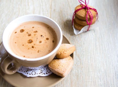 liquified: Cup of coffee with milk and cookies on the table Stock Photo