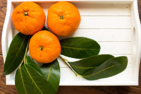 Bunch of fresh tangerines oranges on the wooden