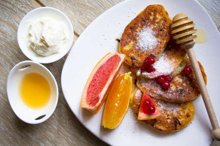 Healthy food, pakcakes with fresh fruits, honey and sour cream, green tea photo