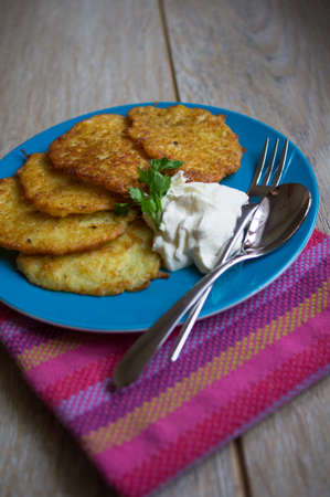 Traditional ukrainian dish - fried potato pancakes or deruny on the plate with sour cream photo