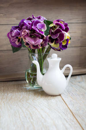 violas: Glasses of green mint tea and vase with fresh violas on the table Stock Photo