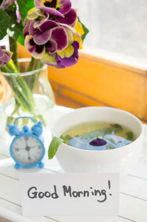 Glasses of green mint tea and vase with fresh violas on the table photo