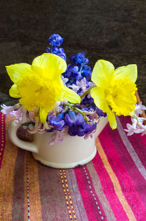 pitcher with hyacinth and narcissus flowers in a vase photo