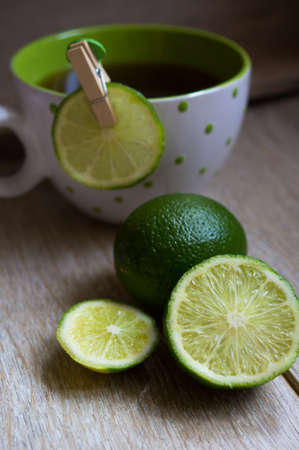 Cup of tea with lime on the wooden table photo