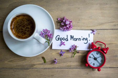 morning coffee: Cup of coffee, Good morning note and lilac flower on the wooden table