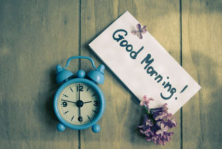 Good morning note, lilac flowers and old-styled clock on the wooden table