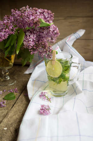 Lilac flowers and fresh mint tea on the wooden table photo
