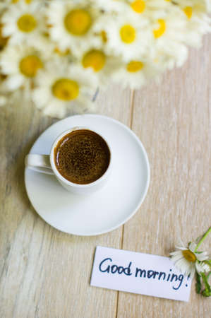 Cup of black coffee and daisy flowers on the old table photo