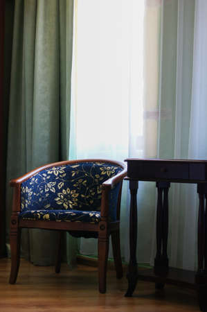 Living room corner with chair and two windows and hardwood floor photo