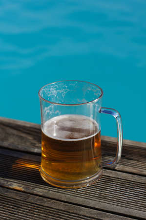 Plain pint glass of cold lager beer sitting on edge of blue swimming pool photo
