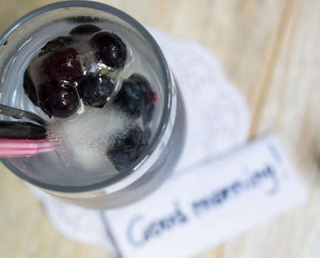 Blueberry juice  cocktail with ice and flowers on the wooden table photo