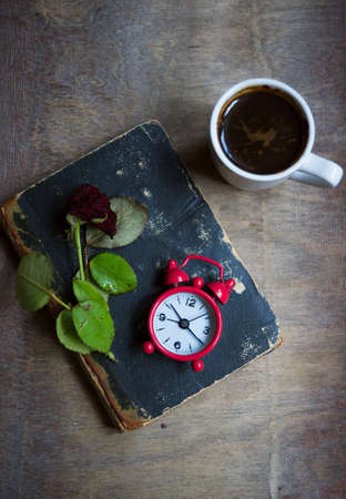 Cup of coffee, old book and dry red rose on the table photo