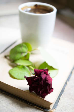 Cup of coffee, old book and dry red rose on the table Stockfoto