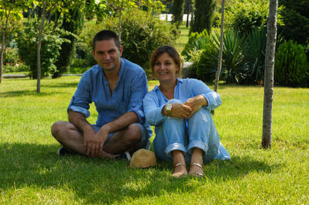 Beautiful Attractive Couple Having Picnic in Countryside. Happy Family Outdoor. Smiling Man and Woman relaxing in Park. Relationships