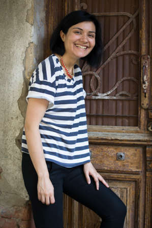 Attractive woman in striped t-shirt at the old door in Old town photo