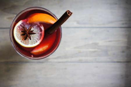 Mulled wine with spices on wooden background photo
