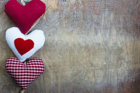 Different color hearts on the wooden background photo