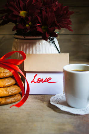 Cup of coffee, flowers, cookies and love note photo