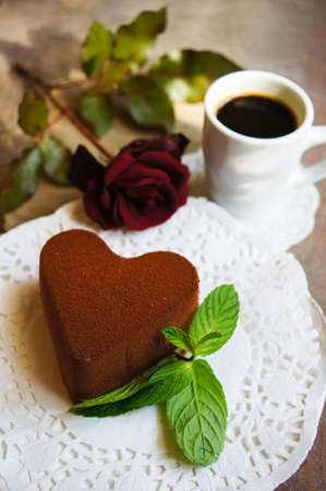 Tiramisu cake heart shaped with fresh mint, tea, red roses and note on the wodden background photo