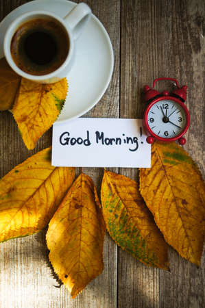 Autumn time, cup of coffee, yellow autumnal leaves and notes photo