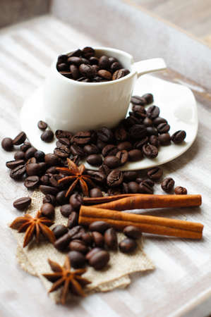 Cup of coffee, cinnamon and anise stars on the wooden table photo
