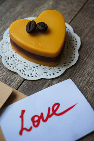 Heart shaped Mocca cake with cup of coffee, coffee beans and Valentine deocrations photo