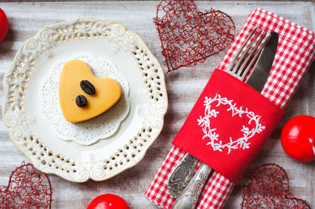 Heart shaped Mocca cake with cup of coffee and Valentine deocrations photo