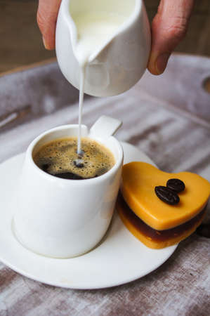 mocca: Someone adds milk to black coffee, and heart shaped mocca cake Stock Photo