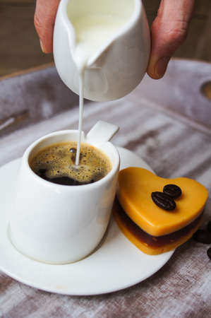 adds: Someone adds milk to black coffee, and heart shaped mocca cake Stock Photo