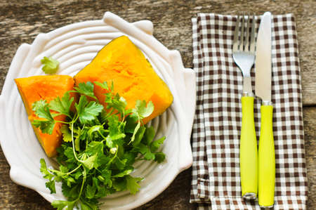 Autumn vegetables - fried pumpkin on the wooden table photo