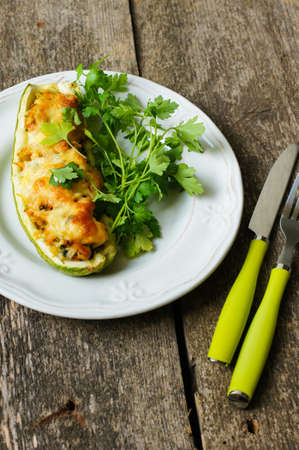 Stuffed zucchini with mushrooms and cheese on a wooden table