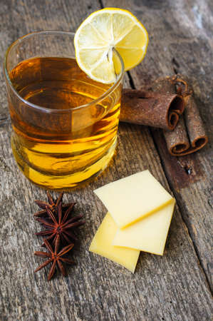 Glass of brandy with lemon, spices and cheese on the old wooden table photo