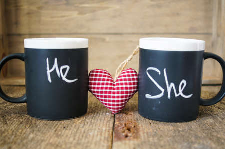he she: Cup with words He and She written with chalk and heart Stock Photo