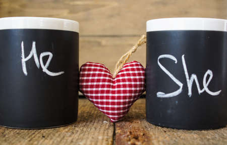 he: Cup with words He and She written with chalk and heart Stock Photo