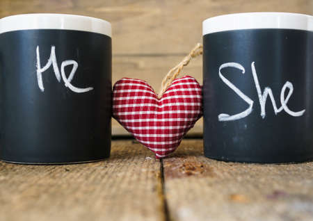 Cup with words He and She written with chalk and heart Stock Photo