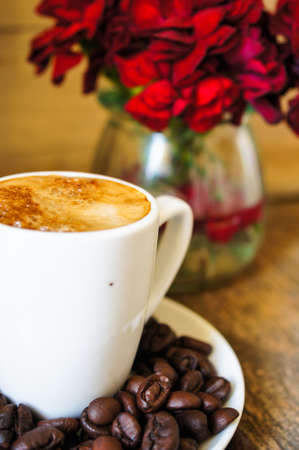 Cup of coffee and red cloves flowers in a vase with good morning note photo