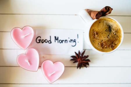 Cup of coffee and red cloves flowers in a vase with good morning note