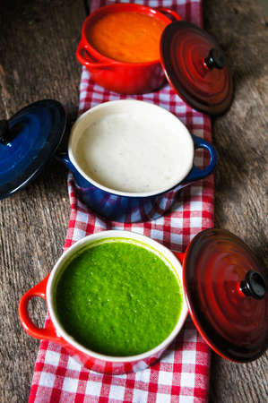 chive: Different kinds of soups - sprinach soup, french onion cream-soup and carrot cream-soup on the table Stock Photo